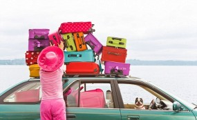 Woman adjusting stack of colorful suitcases on top of car. Image shot 2008. Exact date unknown.
